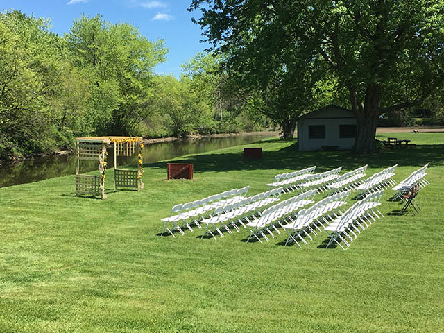 white chairs set for a wedding in the field at the barn at chestnut ridge