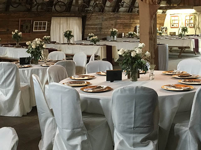 round tables with white chairs at the barn at chestnut ridge